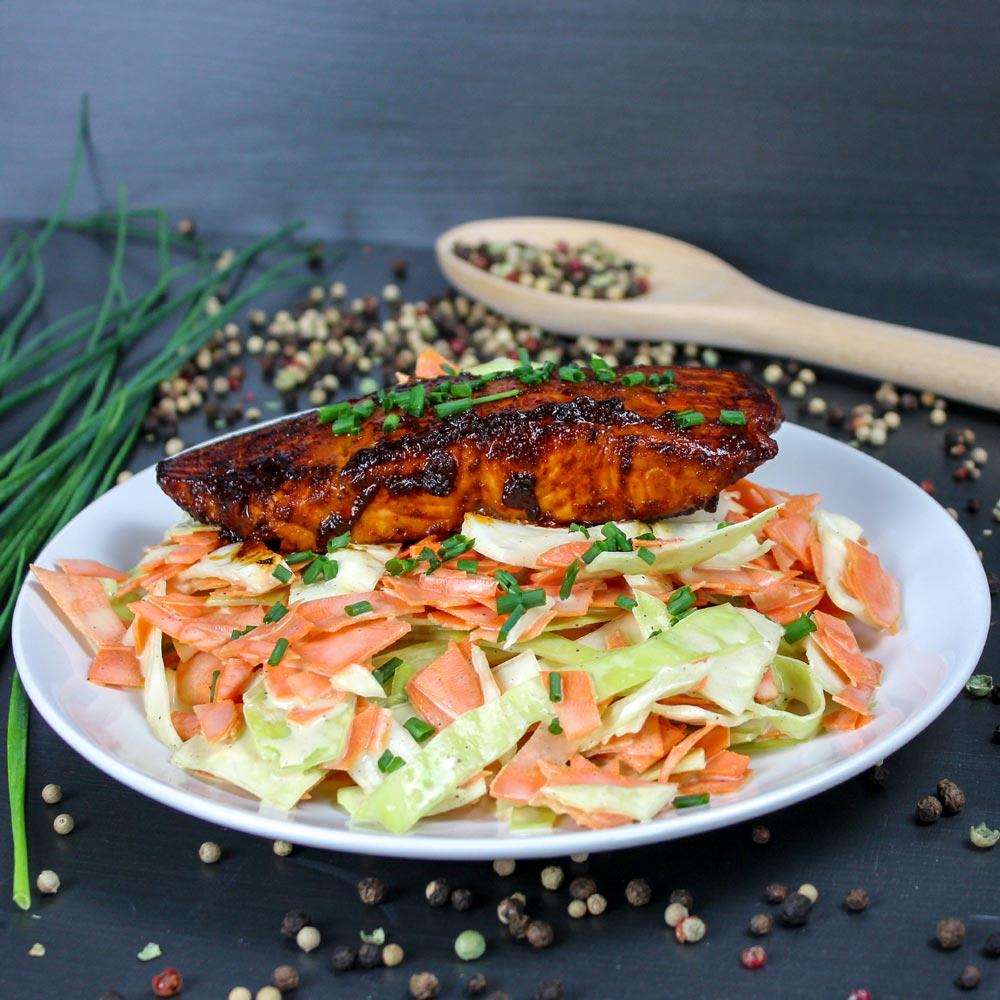 Lachs mit einer Marinade aus BBQ-Sauce und Coleslaw auf einem weißen Teller. Im Hintergrund sind Pfefferkörner und Schnittlauch.