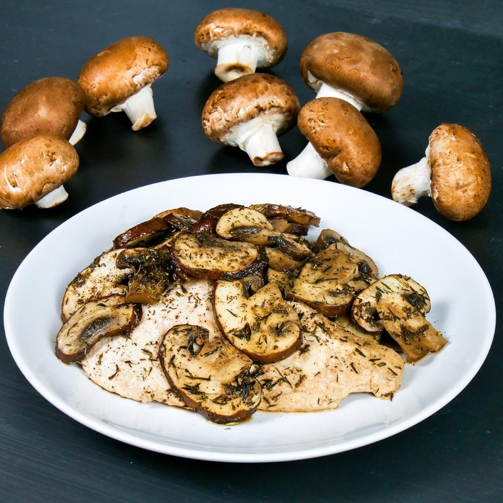 Gebratenes Hähnchenfilet mit braunen Champignons auf einem weißen Teller