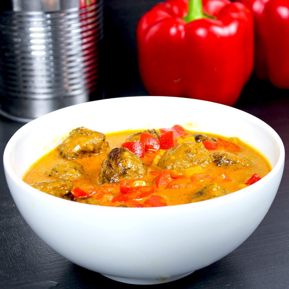 Curry-Gericht mit Hackbällchen und Paprika in einer weißen Schale.