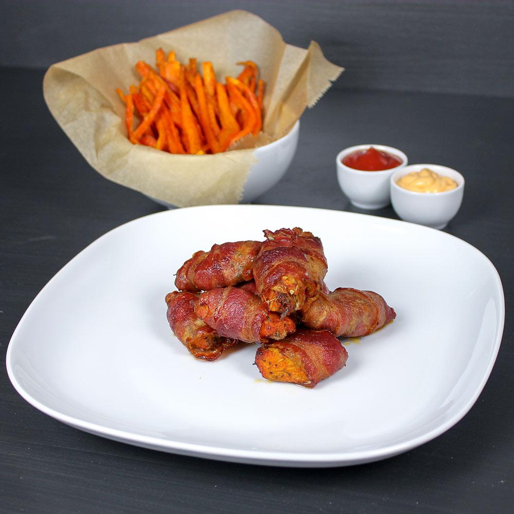 Chicken-Nuggets mit Bacon-Mantel auf einem weißen Teller. Im Hintergrund stehen Karotten-Pommes.