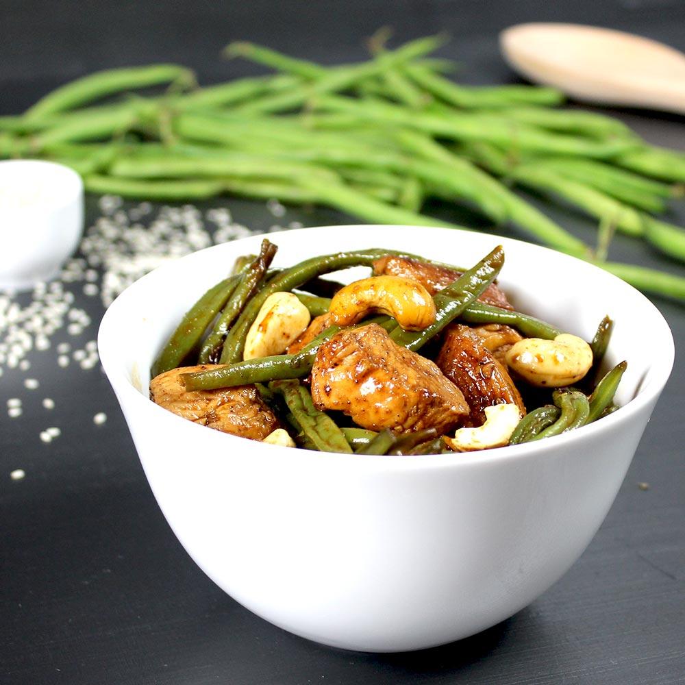 Ein Gericht aus Hähnchen und grünen Bohnen in einer weißen Schüssel. Im Hintergrund liegen Bohnen.