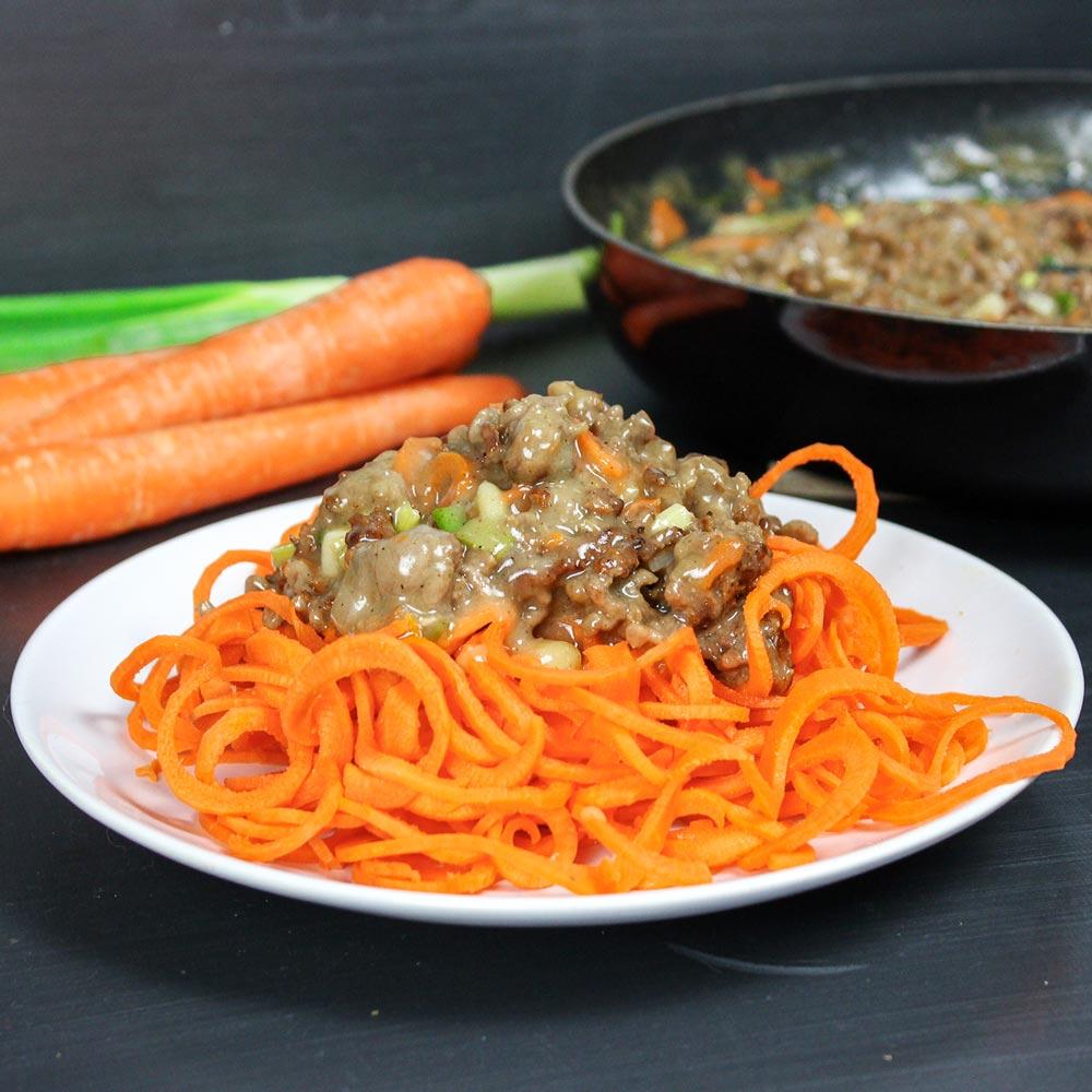 Weißer Teller mit Karottennudeln und einer hellen Bolognese-Soße. Im Hintergrund steht die Pfanne mit der Soße.