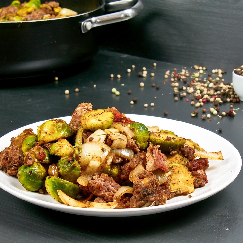 Pfannengericht mit Rosenkohl, HHackfleisch und Bacon auf einem weißen Teller. Im Hintergrund steht die Pfanne mit dem Gericht.