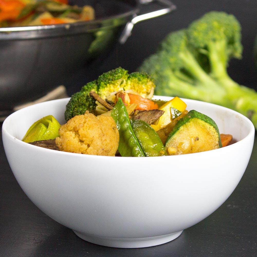 Schüssel mit einem Wok-Gericht aus Gemüse und Rindfleisch. Im Hintergrund steht der Wok, in welchem das Gericht zubereitet wurde.
