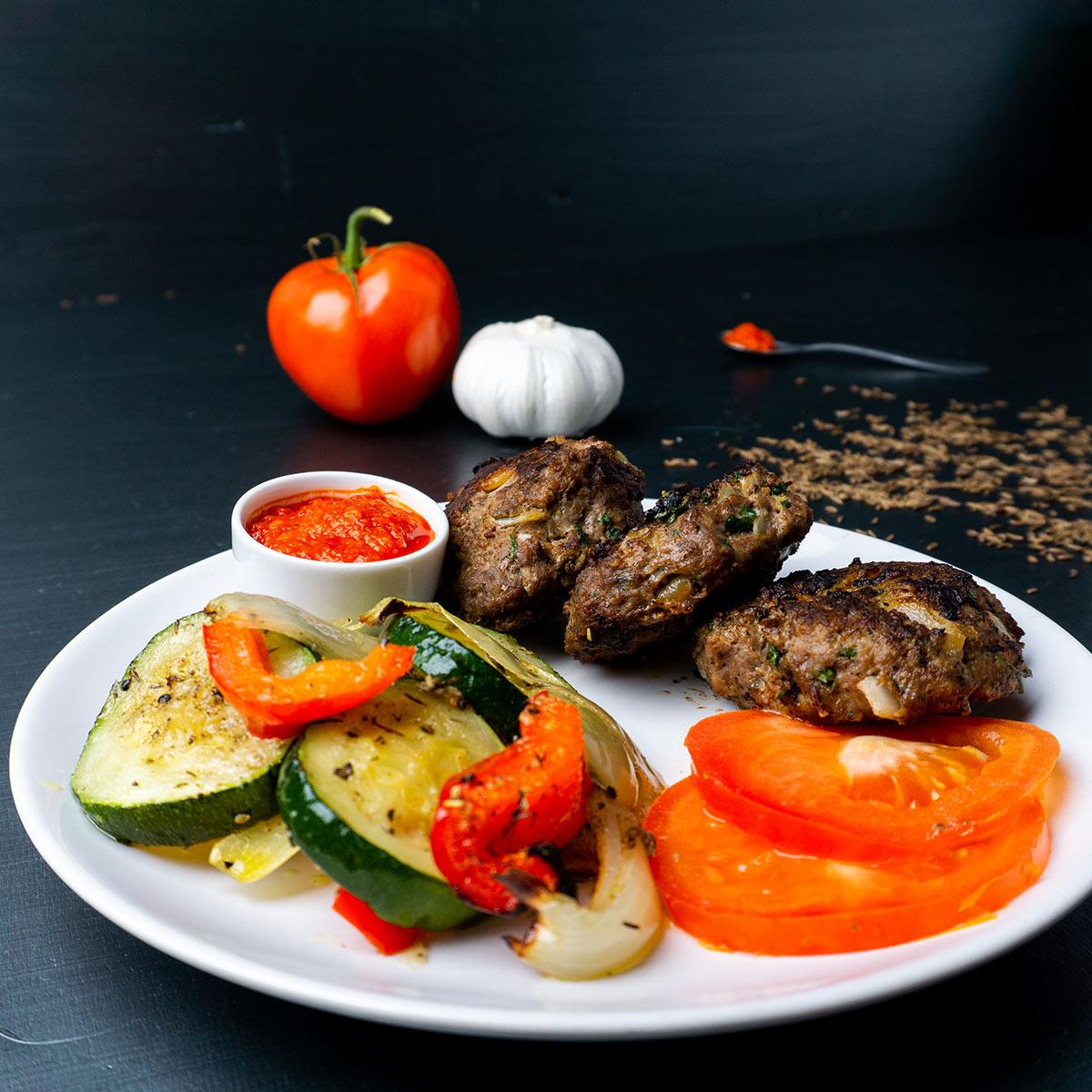 Ein weißer Teller mit Köfte, Ofengemüse und Aivar