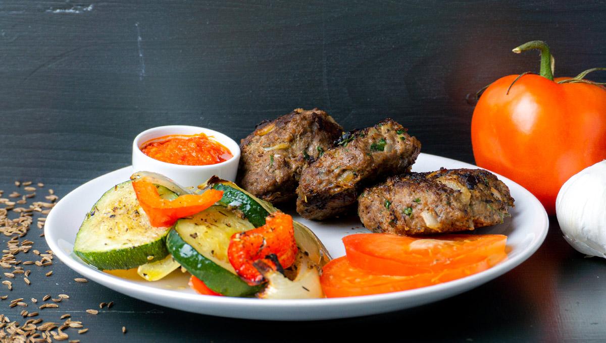 Köfte auf einem Teller mit Ofengemuese und Tomatenscheiben